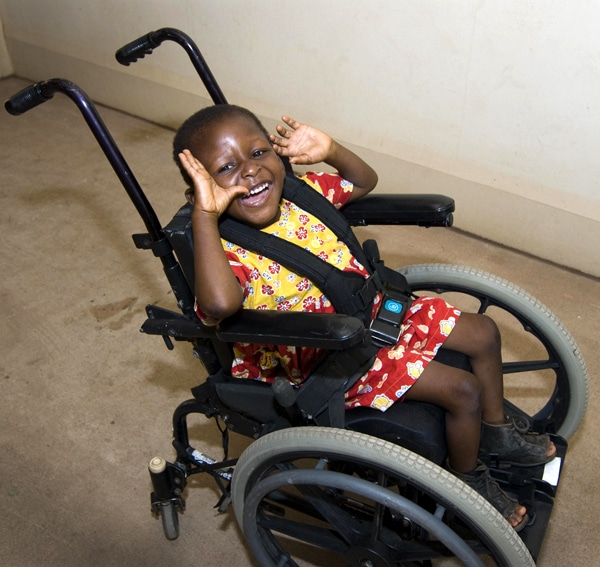 african girl in her new wheelchair with a big smile on her face