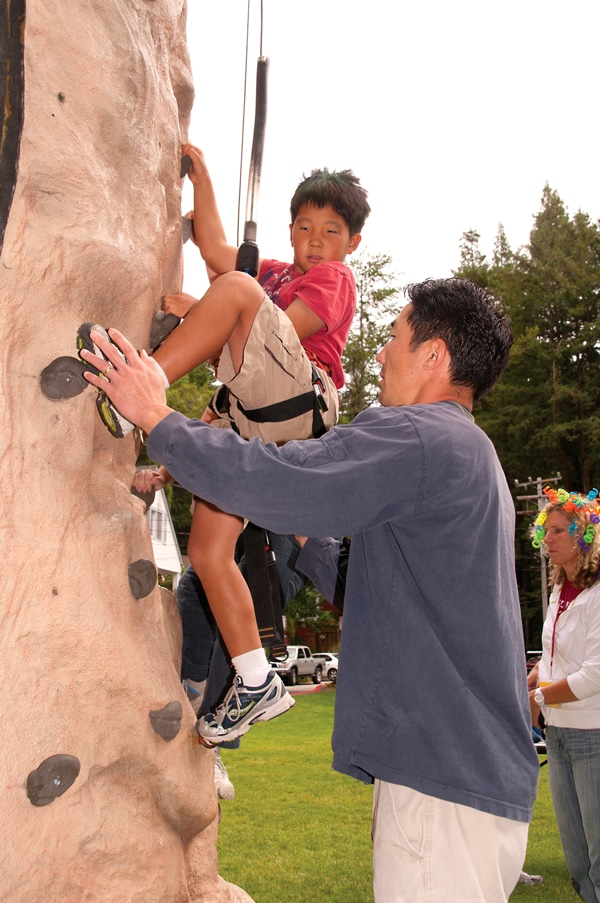 Jeremy climbing the wall with his dad's support