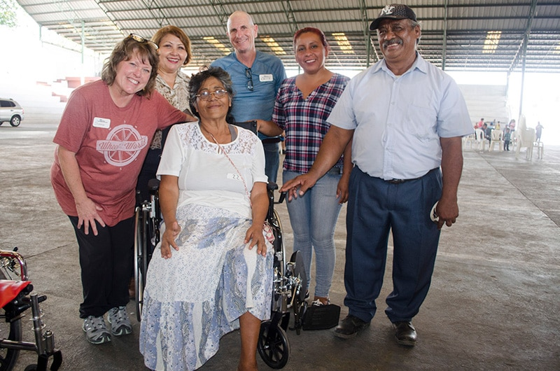 A group of volunteers take a picture with a new wheelchair recipient